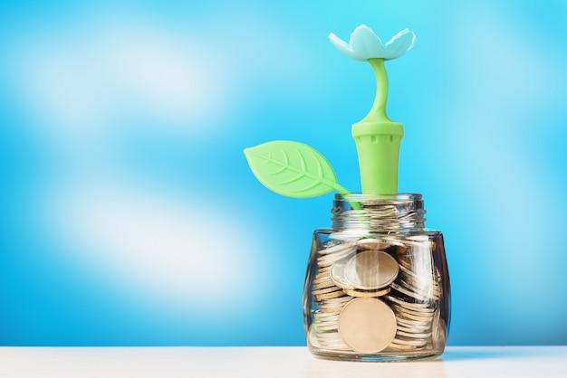 Glazen pot gevuld met munten met bloem en blad. investeringsgroei concept.