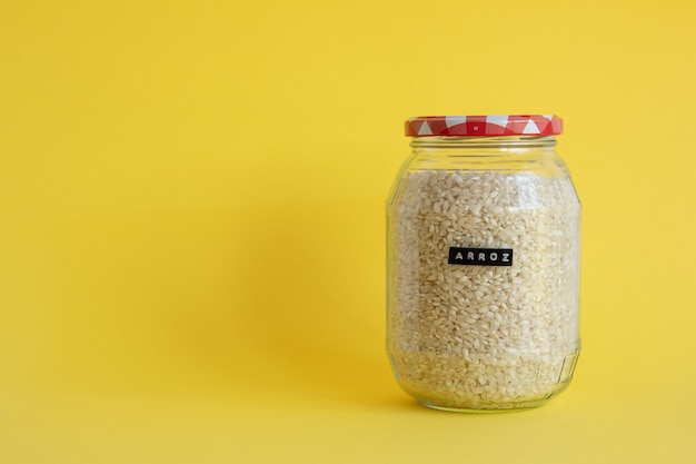 Glazen pot gevuld met rijst geïsoleerd op gele achtergrond