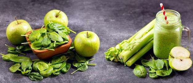 Glazen pot groene sap smoothie met spinazie, appel en selderij op donker