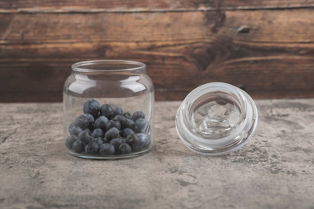 Glazen pot heerlijke verse bosbessen op marmeren oppervlak
