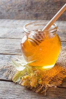 Glazen pot honing, linden bloemen op houten achtergrond