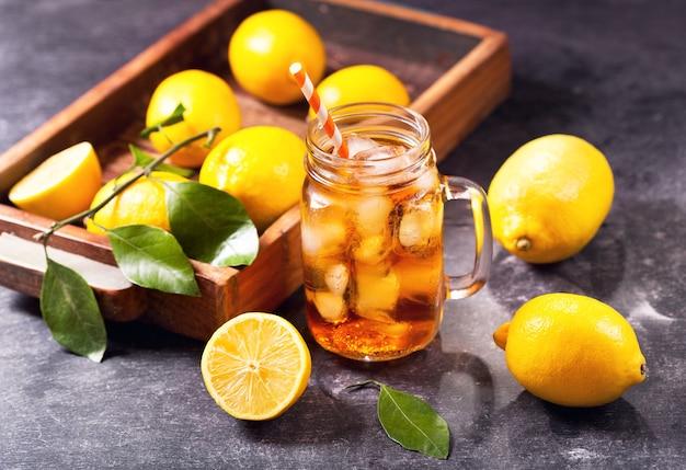 Glazen pot ijsthee met verse citroenen op donker