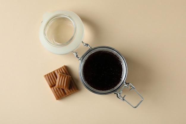 Glazen pot karamelsaus en stukjes karamel op beige achtergrond