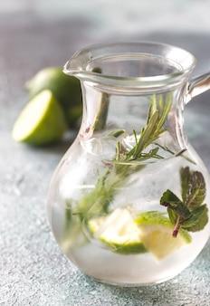 Glazen pot limoenwater met kruiden
