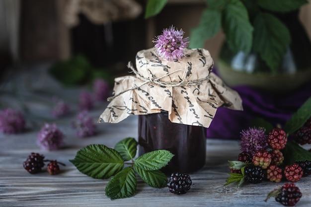 Glazen pot met blackberry saus close-up. tak met bessen en bladeren in een houten gesneden doos op een donkere houten