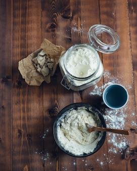 Glazen pot met bloem en kom met zuurdesem. bakkerij concept. kopieer ruimte.
