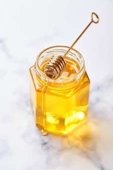 Glazen pot met bloemen vloeibare honing en metalen honinglepel op lichte marmeren achtergrond. alternatieve suikervervanger, verkoudheidsremedie en lichaamsversterking, superfood