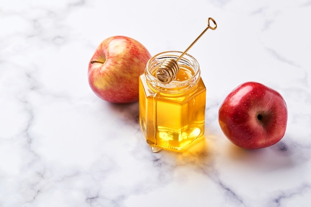 Glazen pot met bloemen vloeibare honing met metalen honinglepel en twee rode appels op lichte marmeren achtergrond. alternatieve suikervervanger, verkoudheidsremedie en lichaamsversterking, superfood