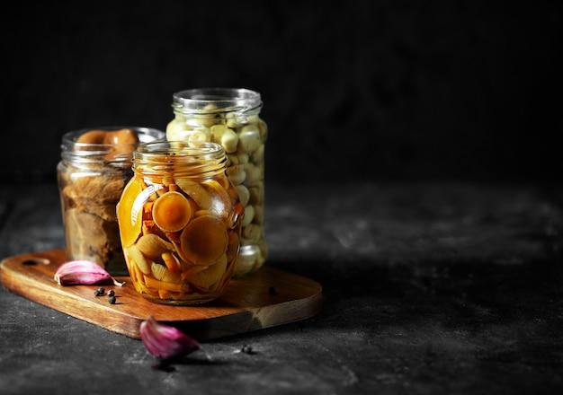 Glazen pot met champignons in blik met knoflook en peper.