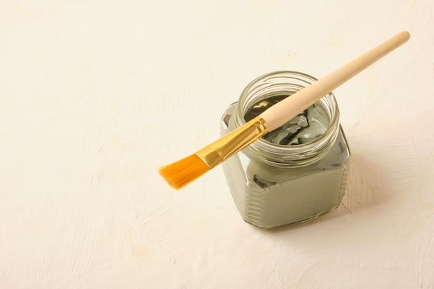 Glazen pot met cosmetische klei en een penseel voor toepassing, beige achtergrond kopie ruimte, trendkleuren