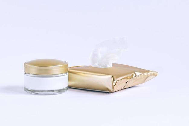 Glazen pot met crème en gezichtsreinigingsdoekjes