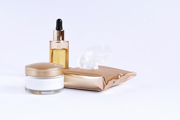 Glazen pot met crème, schoonmaakdoekjes en glazen fles met een pipet met gezichtsserum