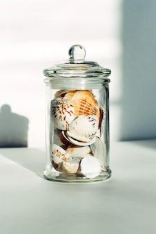 Glazen pot met een verscheidenheid aan schelpen. decor voor het interieur in scandinavische stijl.