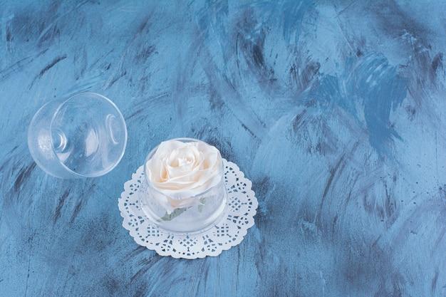 Glazen pot met enkele witte roos op blauw.