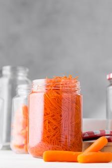 Glazen pot met gehakte worteltjes