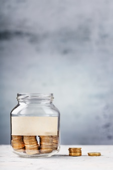 Glazen pot met gouden munten en tekst sticker op grijs met vrije ruimte voor tekst.