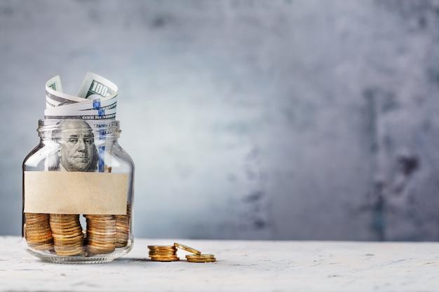 Glazen pot met gouden munten, met een honderd dollar biljet en een sticker voor tekst op grijs met vrije ruimte voor tekst.