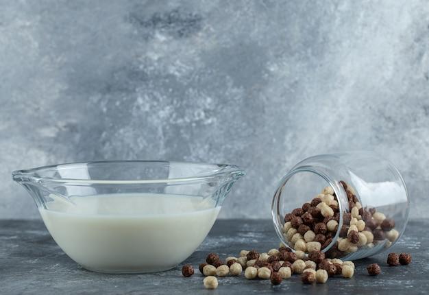 Glazen pot met granenballen en melk op marmer.