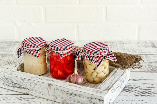 Glazen pot met ingeblikte knoflook, gember en mierikswortel. gefermenteerd voedsel op een witte achtergrond.