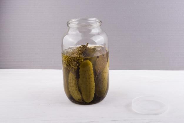 Glazen pot met ingelegde komkommers op grijze achtergrond