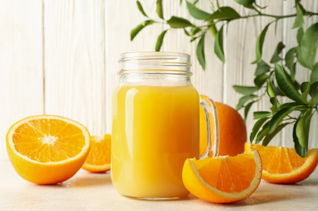 Glazen pot met jus d'orange tegen witte houten tafel