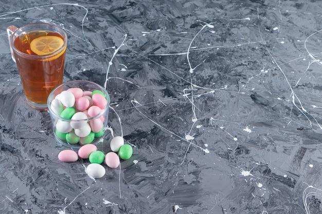 Glazen pot met kleurrijke bonbons en kopje zwarte thee op marmeren achtergrond.