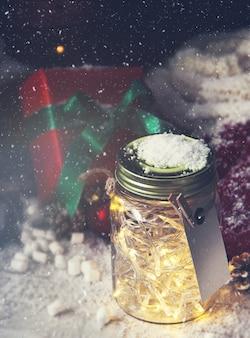 Glazen pot met lampen met een gift ernaast, terwijl het sneeuwt van boven gezien