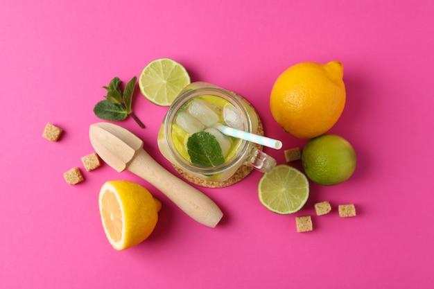 Glazen pot met limonade en ingrediënten op roze oppervlak