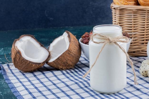 Glazen pot met melk en half gesneden kokosnoten op marmeren tafel.