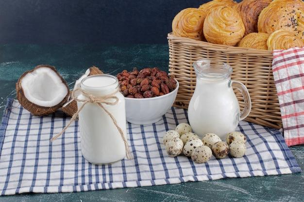 Glazen pot met melk, gedroogde dadels en kwarteleitjes op marmeren tafel.