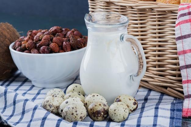 Glazen pot met melk, gedroogde dadels en kwarteleitjes op tafellaken.