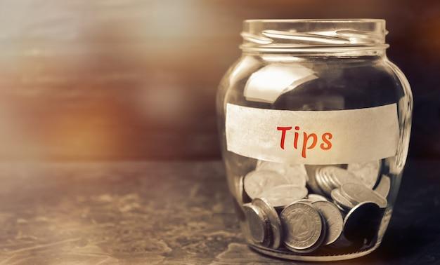 Glazen pot met munten en de inscriptie tips