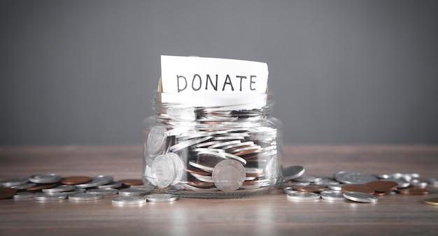 Glazen pot met munten en doneer woord.