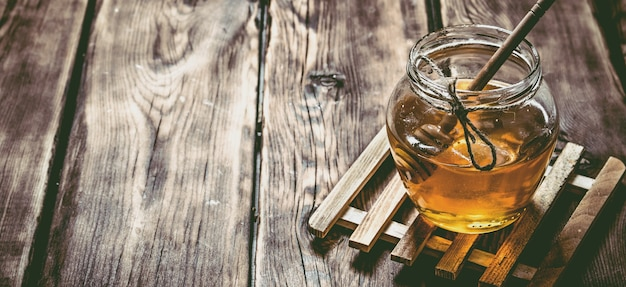 Glazen pot met natuurlijke honing en een lepel op houten tafel.