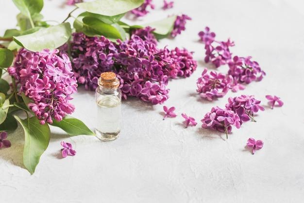 Glazen pot met rozenwater en lila bloemen