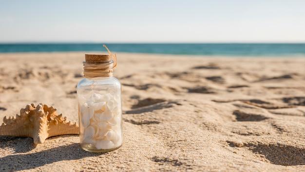 Glazen pot met schelpen en zeester op kust