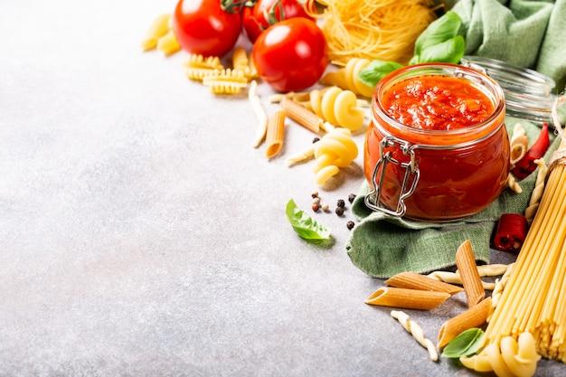 Glazen pot met zelfgemaakte klassieke pittige tomatenpasta of pizzasaus.