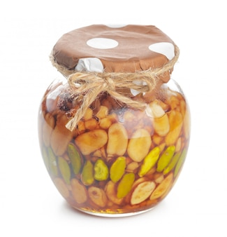 Glazen pot met zoete honing geïsoleerd