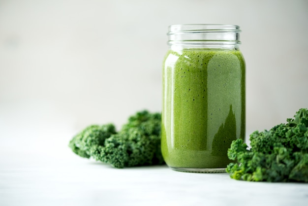 Glazen pot mokken met groene gezondheid smoothie, boerenkool bladeren, limoen, appel, kiwi, druiven, banaan, avocado, sla.
