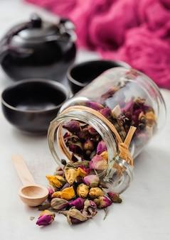 Glazen pot rozenknoppen mix thee met houten lepel op witte achtergrond met zwarte theepot en kopjes.