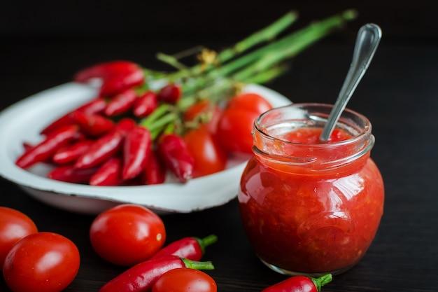 Glazen pot tomatensaus met verse ingrediënten