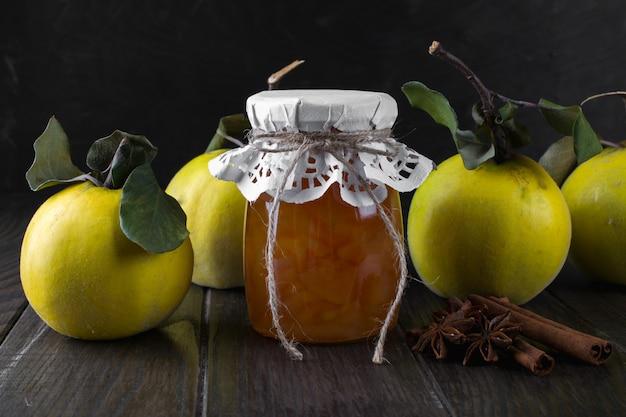 Glazen pot van zelfgemaakte kweepeer jam met vers fruit op tafel
