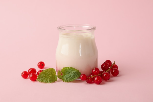 Glazen pot van zure room yoghurt en amerikaanse veenbes op roze