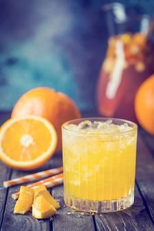 Glazen pot vers sinaasappelsap met ijs en vers fruit op donkere tafel