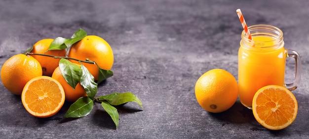 Glazen pot vers sinaasappelsap met vers fruit op donkere tafel