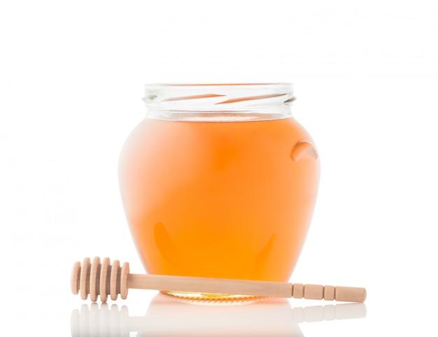 Glazen pot vol met honing en houten stok op het geïsoleerd op een witte achtergrond