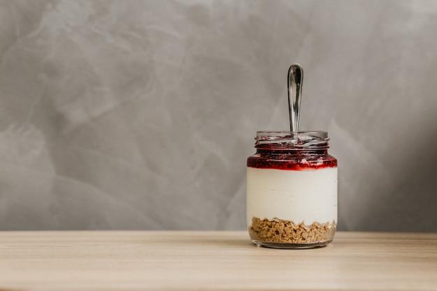 Glazen pot vol ontbijtgranen, yoghurt en fruitjam met een lepel erin