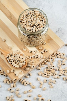 Glazen pot witte kidneybonen op een houten bord.