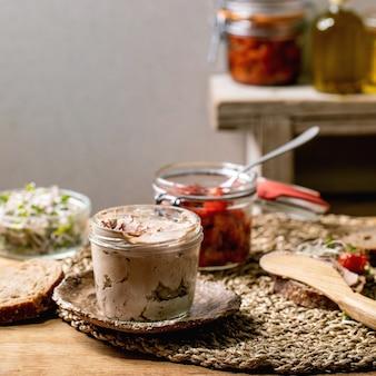 Glazen pot zelfgemaakte kippenleverpastei met gesneden roggebrood, zongedroogde tomaten en groene spruitensalade op houten keukentafel. thuis ontbijt of voorgerecht. vierkante afbeelding