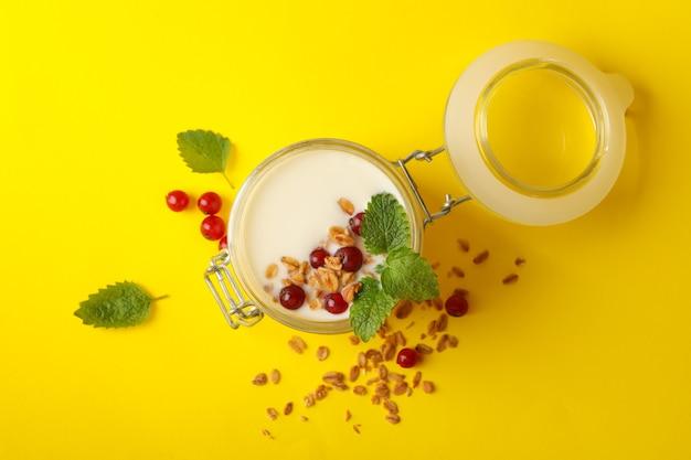Glazen pot zure room yoghurt met cranberry, munt en granola op geel